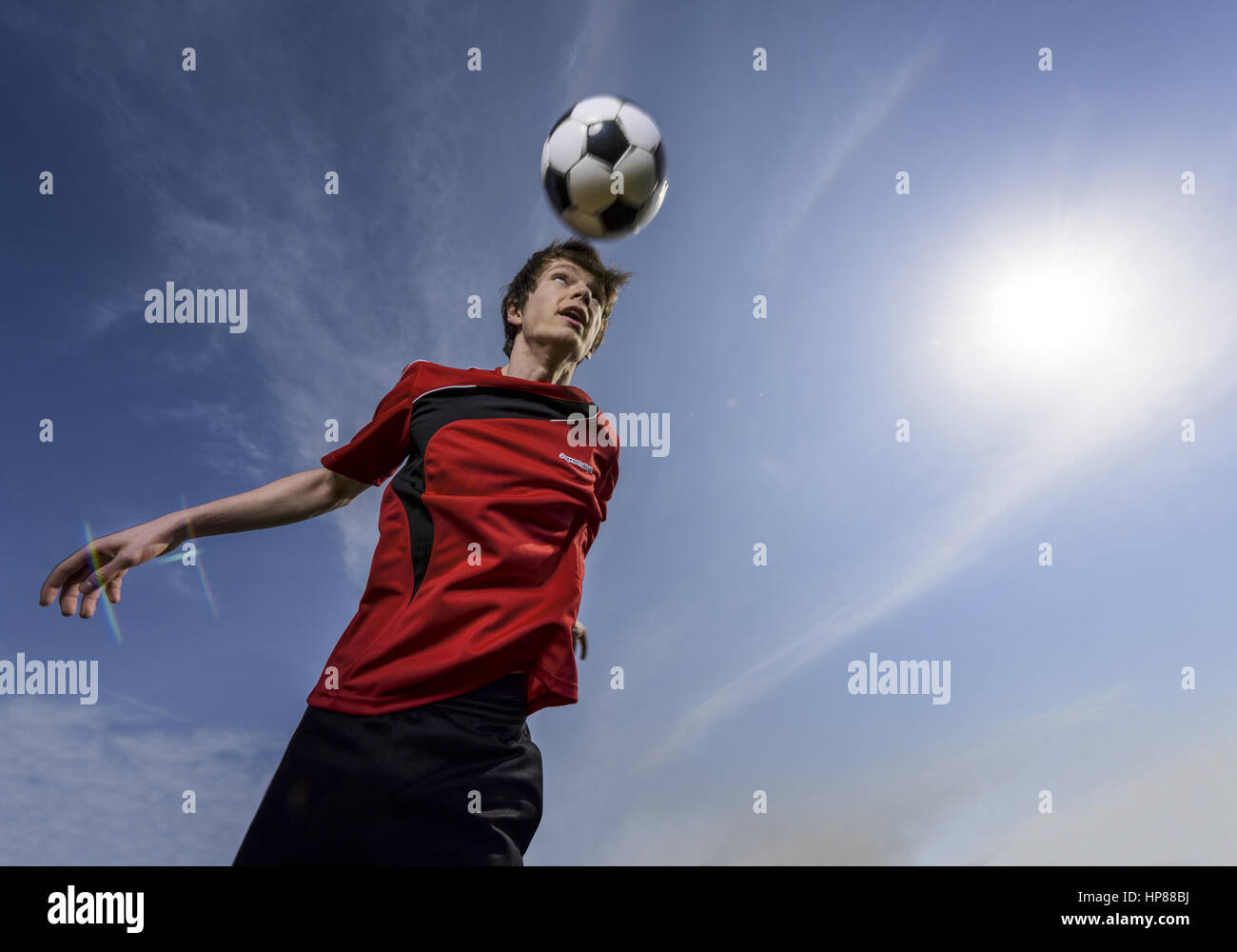 Fussballer koepft Ball (model-released) - Stock Image