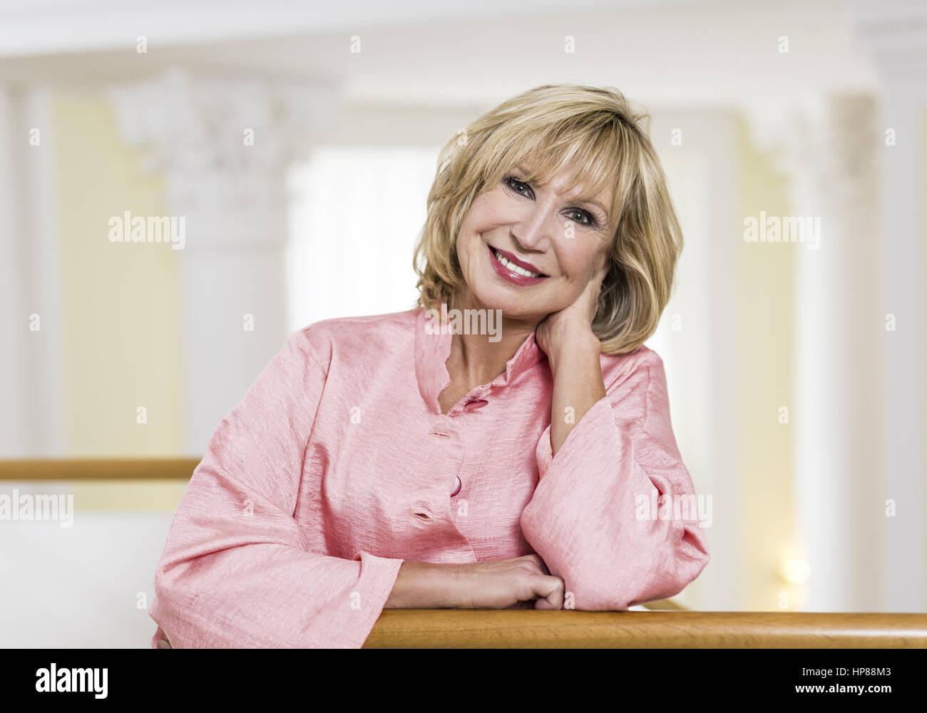 Blonde Frau in eleganter rosa Jacke (model-released) - Stock Image