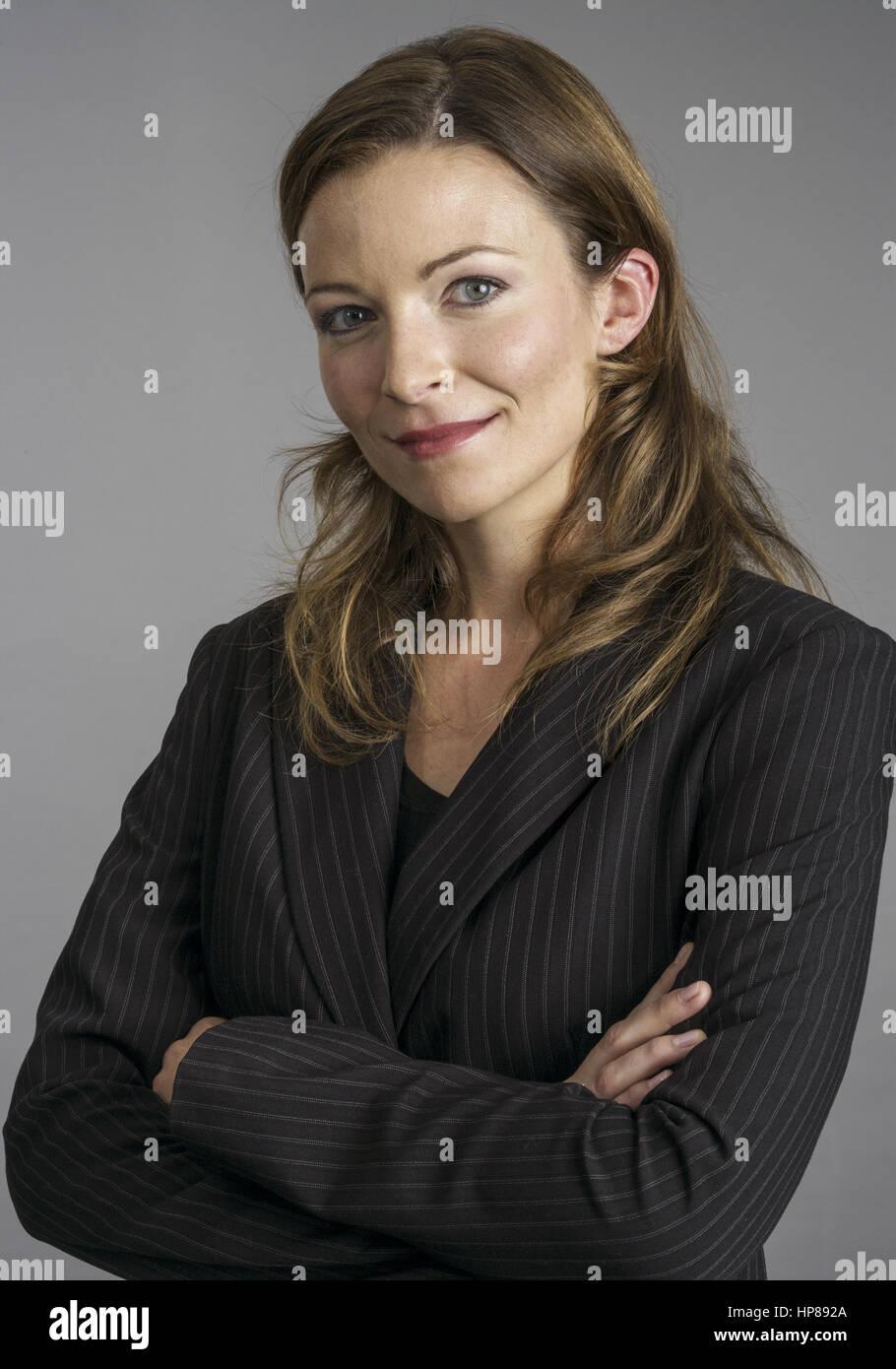 Frau im Anzug, verschraenkte Arme, Halbportraet (model-released) Stock Photo