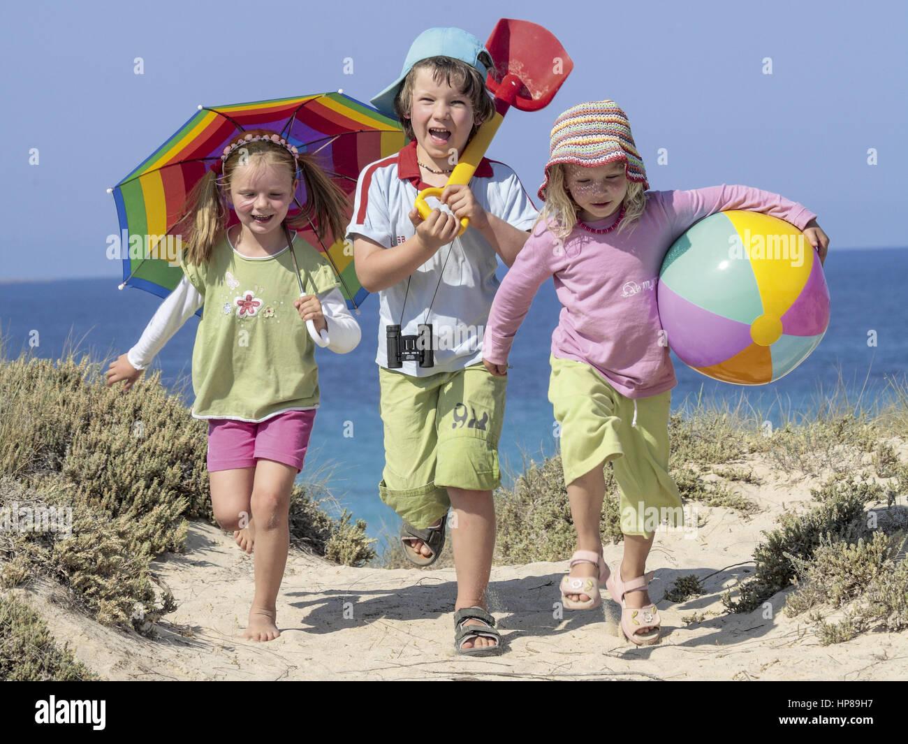 Drei Kinder laufen am Meer ueber Duenen (model-released) - Stock Image