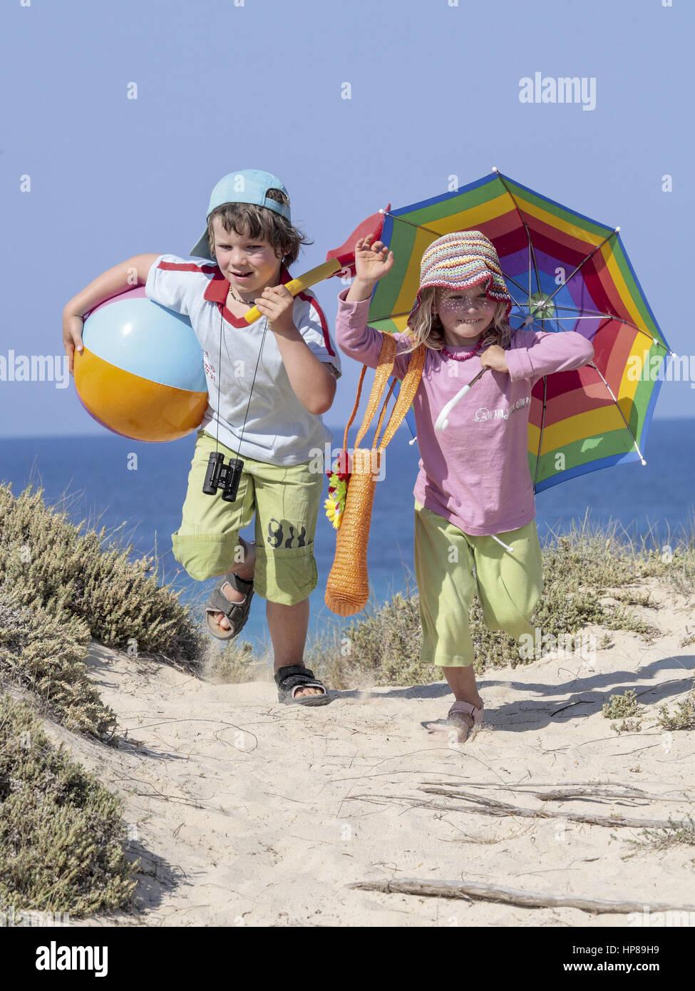 Zwei Kinder laufen am Meer ueber Duenen (model-released) - Stock Image