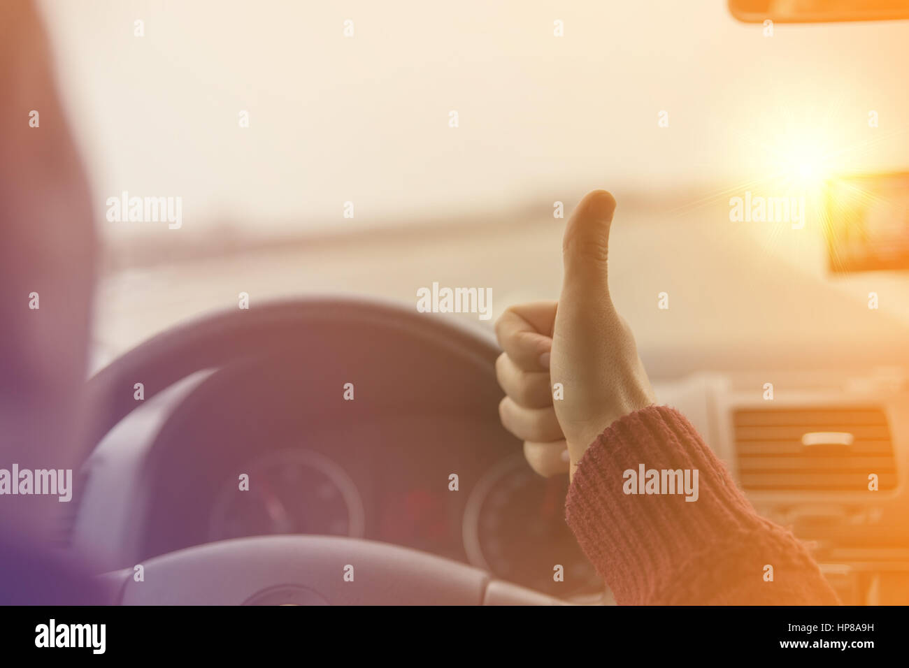 Man Driving A Car on a Highway and Raising His Thumbs. Sunny day - Stock Image