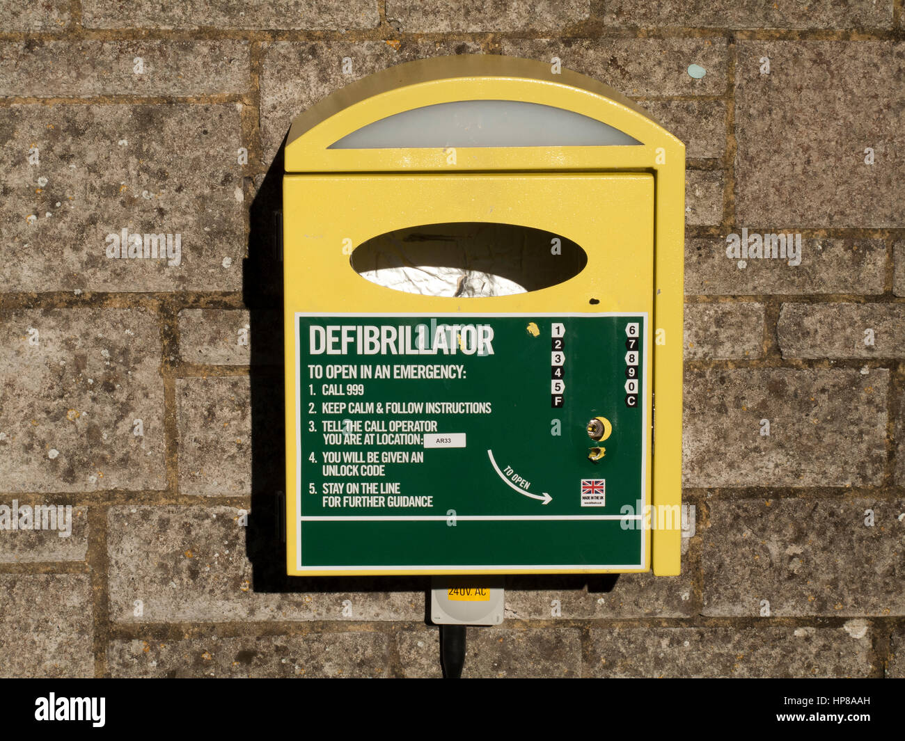 Medical defibrillator mounted on stone wall for use by the general public with instructions - Stock Image
