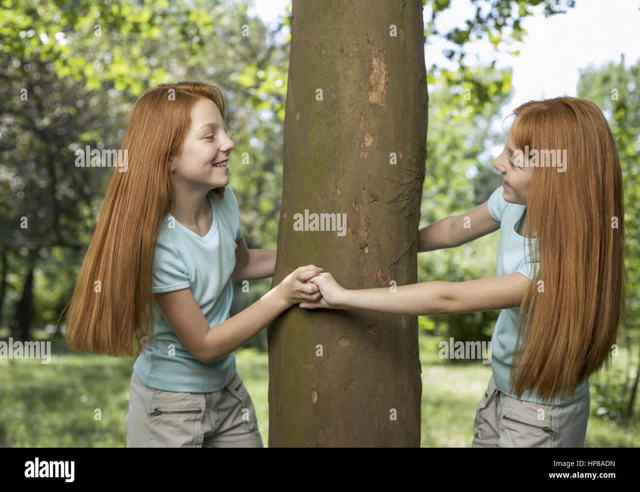 Rothaarige Zwillingsmaedchen spielen an Baumstamm (model-released) - Stock Image
