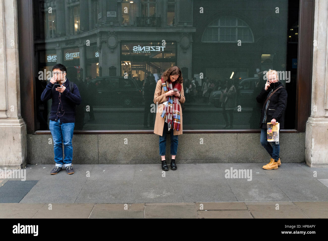 Three young people using mobile phones in street - Stock Image
