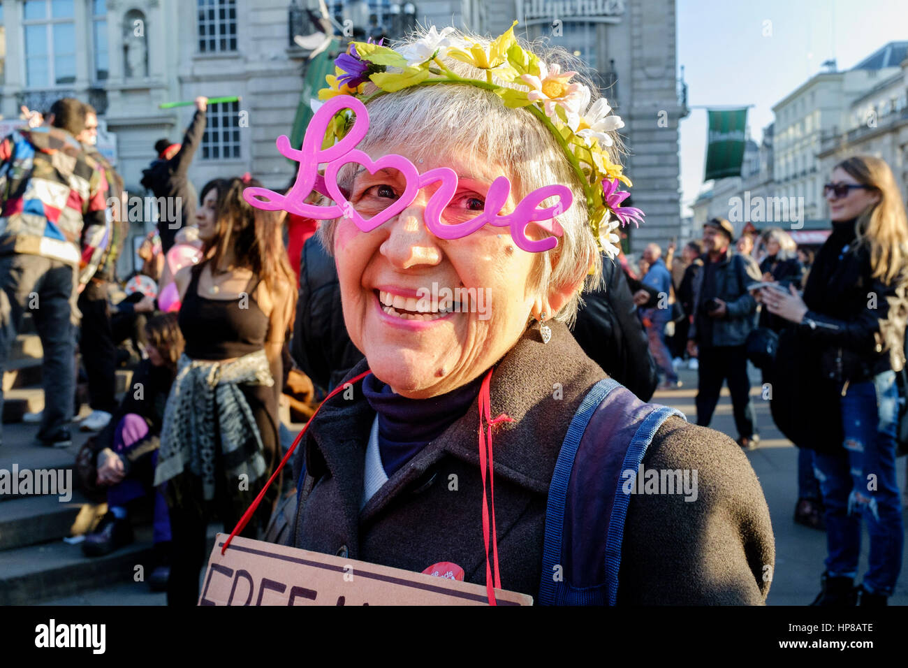 Mature woman wears novelty LOVE spectacles at the Reclaim Love pavement party, Leicester Square, London, UK - Stock Image