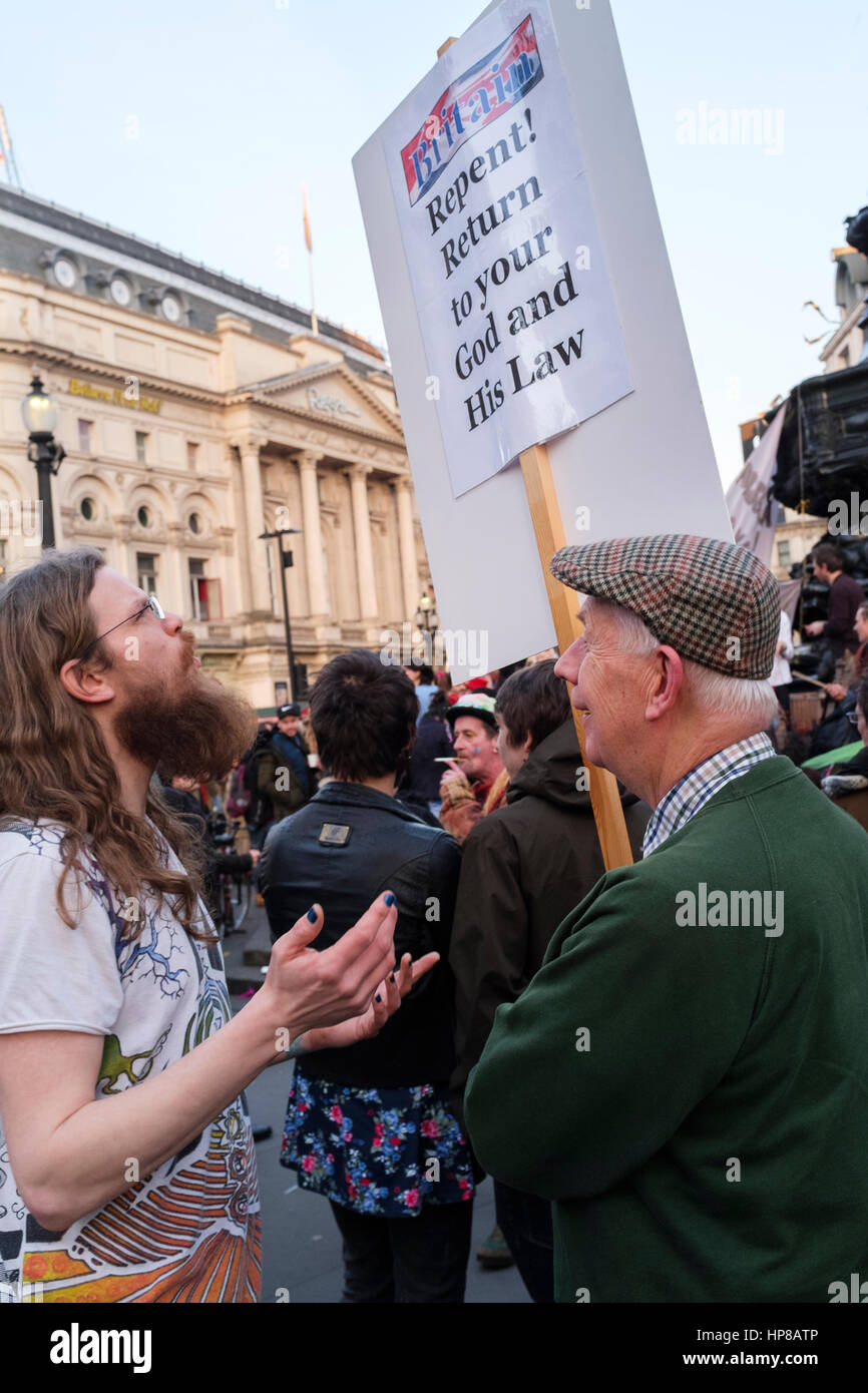 Christian evangelist carrying religious placard converses with young man, London, UK - Stock Image