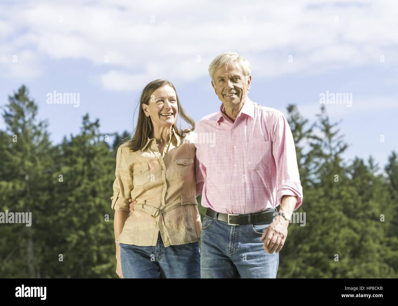 Seniorenpaar beim Spazierengehen an Waldrand (model-released) - Stock Image
