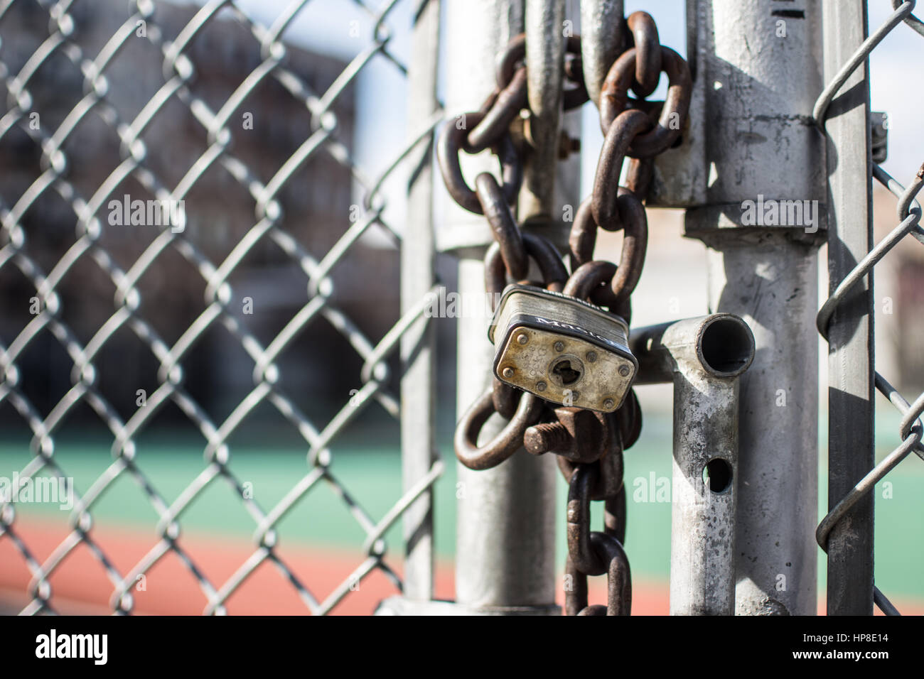 Locked gate with padlock and chain - chain link fence background taken in Inwood NYC Manhattan. - Stock Image