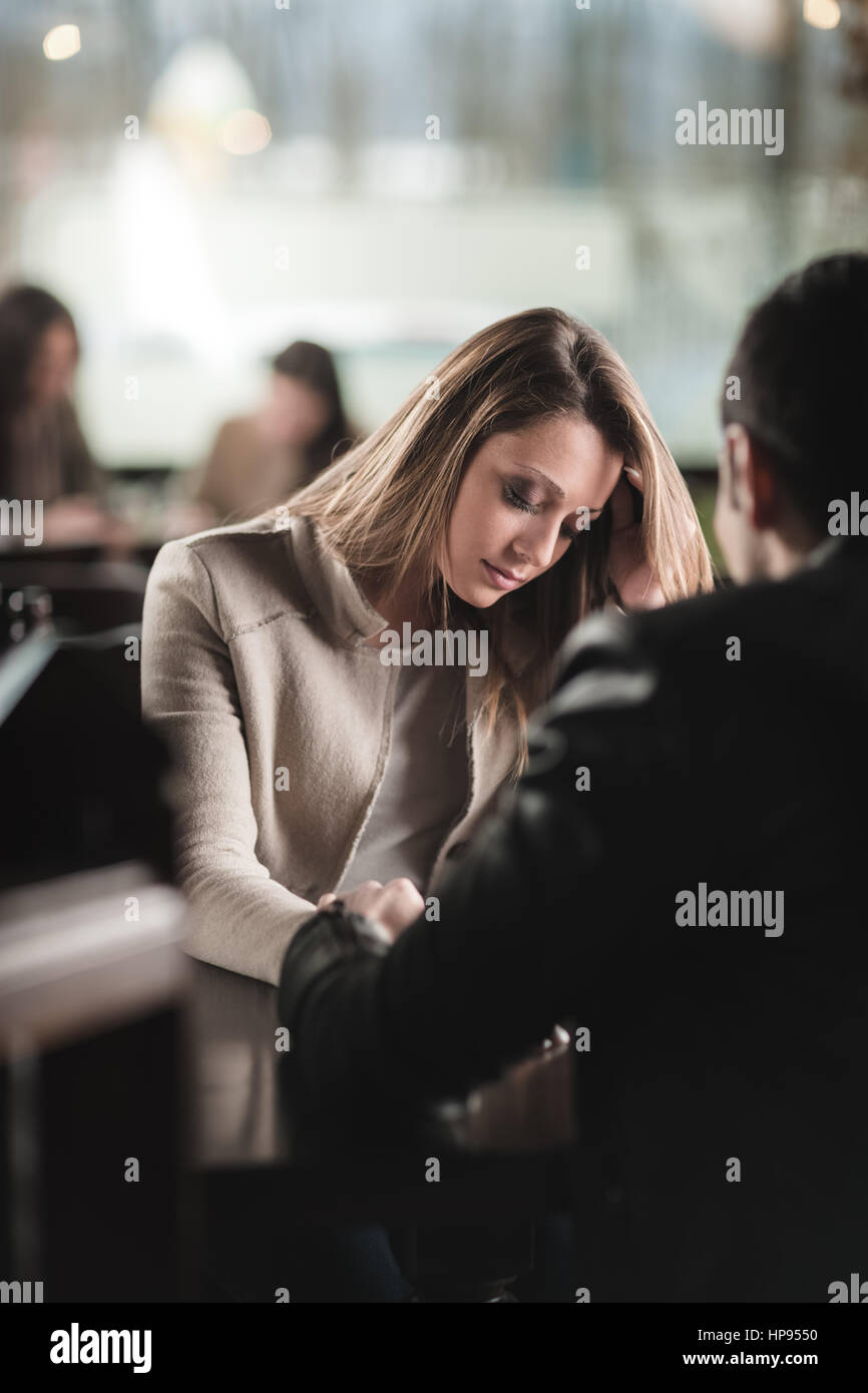 Young couple at the bar he is consoling his sad girlfriend - Stock Image