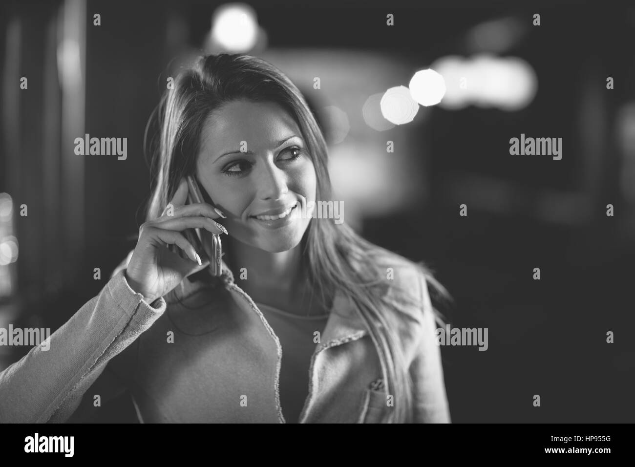 Smiling young woman at the bar having a phone call with her mobile phone - Stock Image