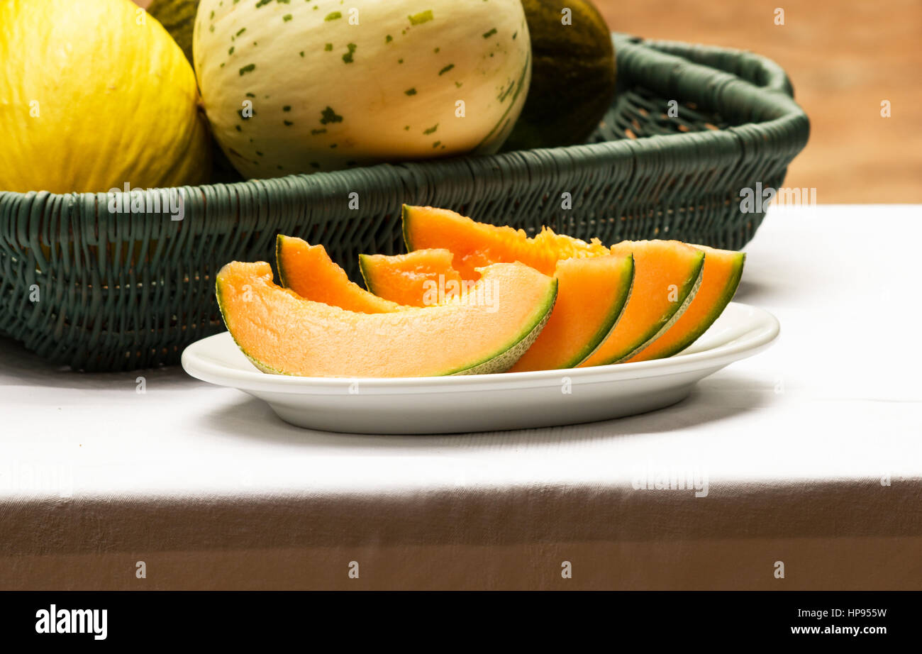 Basket with different types od melon and plate with sliced melon. - Stock Image