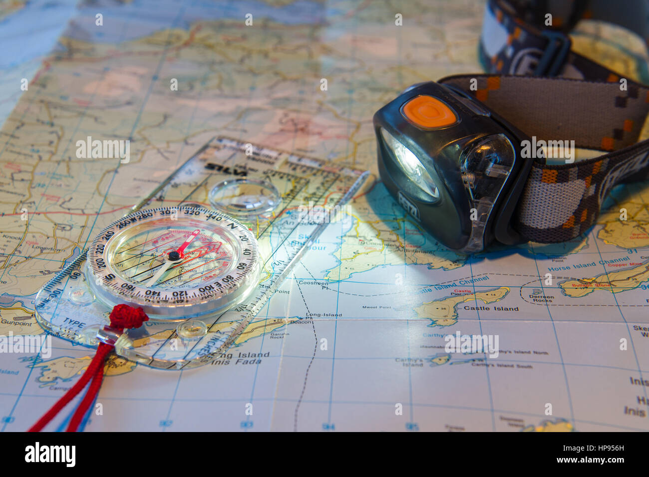 Petzl headtorch and a Silva Compass on a map of Ireland. - Stock Image