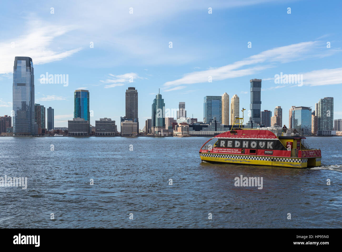 A NY Waterway ferry departs the World Financial Center Ferry Terminal, with the skyline of Jersey City in the background - Stock Image