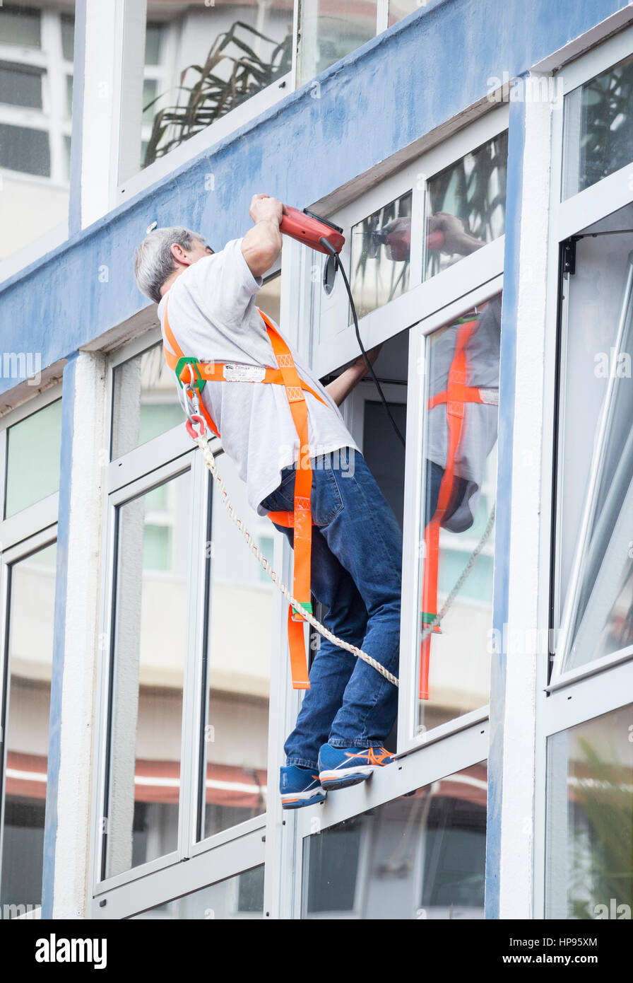 Man using power tool balancing precariously on window ledge. - Stock Image