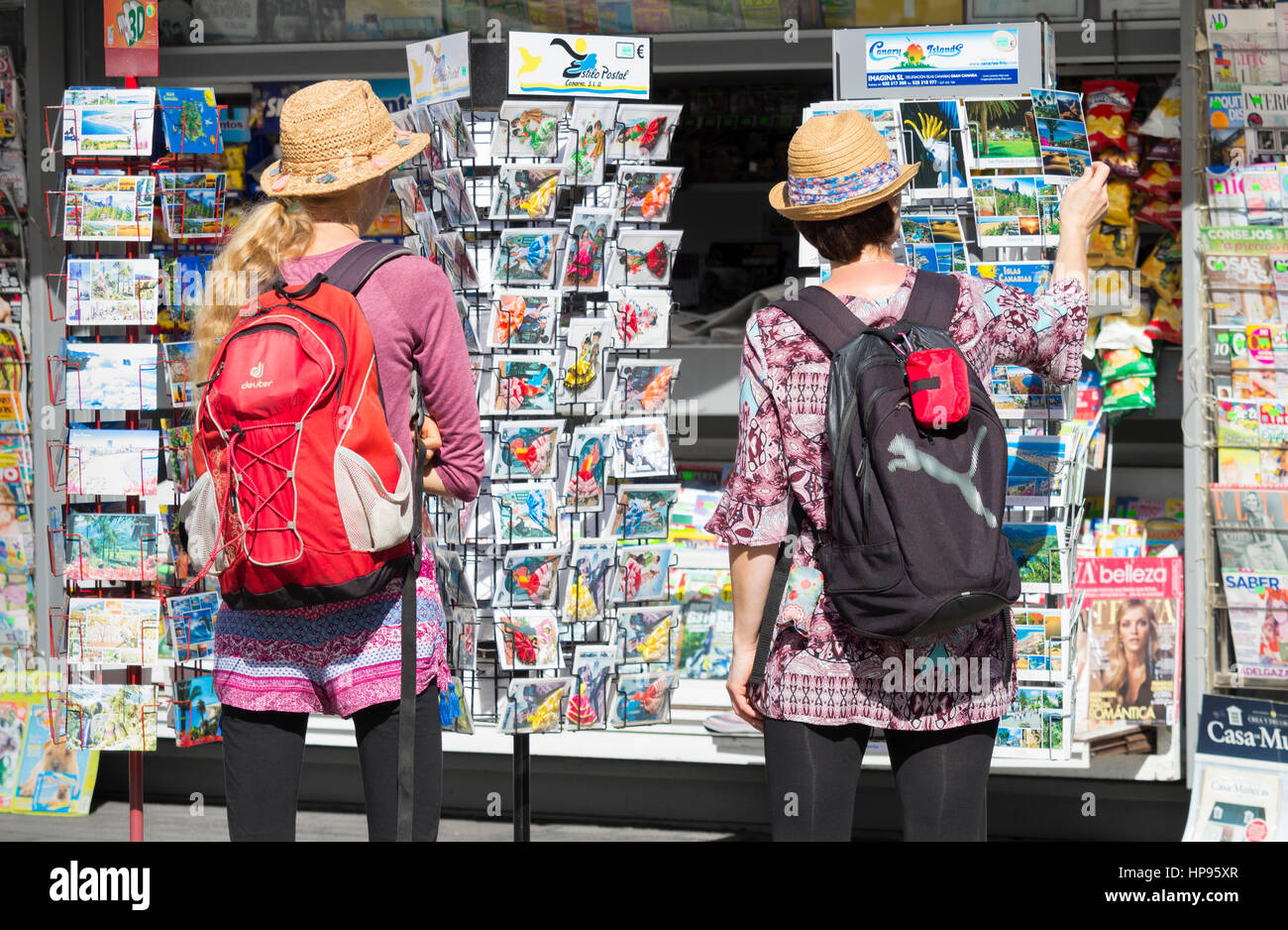 Female tourists looking at postcards. - Stock Image