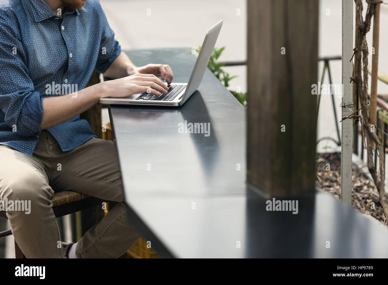 Unrecognizable man using a modern portable computer on an outdoor table, street on background - Stock Image