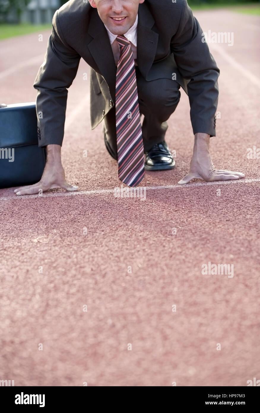 Model released , Gesch?ftsmann an der Startlinie auf einer Laufbahn - businessman on strating line - Stock Image