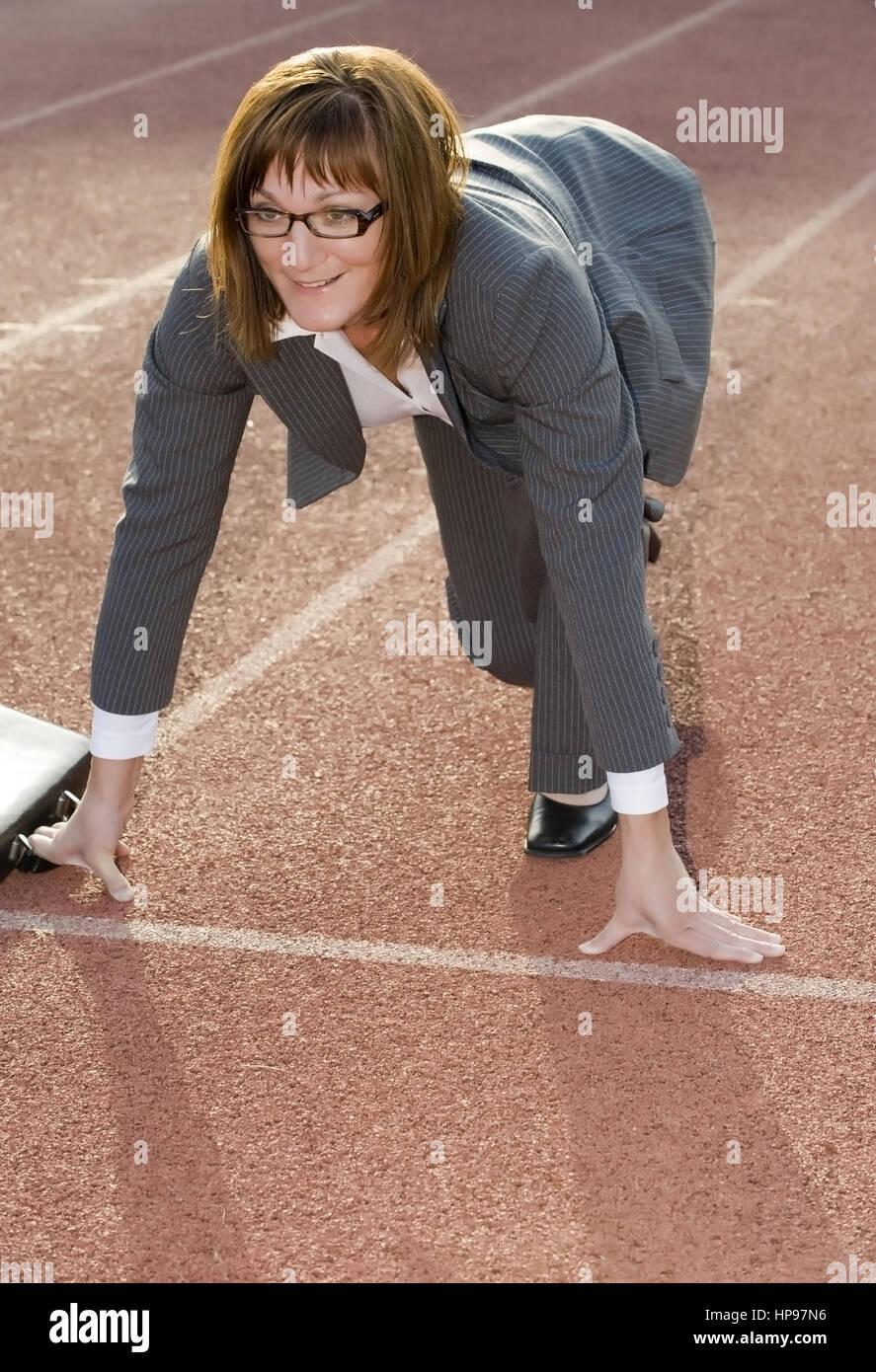 Model released , Gesch?ftsfrau an der Startlinie auf einer Laufbahn, Symbolbild Berufliche Laufbahn - businesswoman - Stock Image