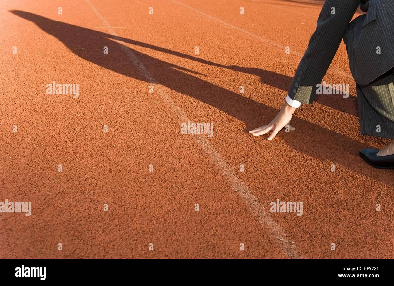 Model released , Gesch?ftsfrau in Startposition auf der Laufbahn - business woman on running track - Stock Image