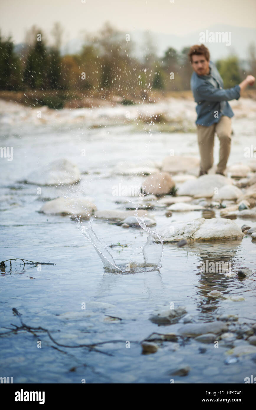 Young man throwing stones in the river and water splash, nature and freedom concept - Stock Image