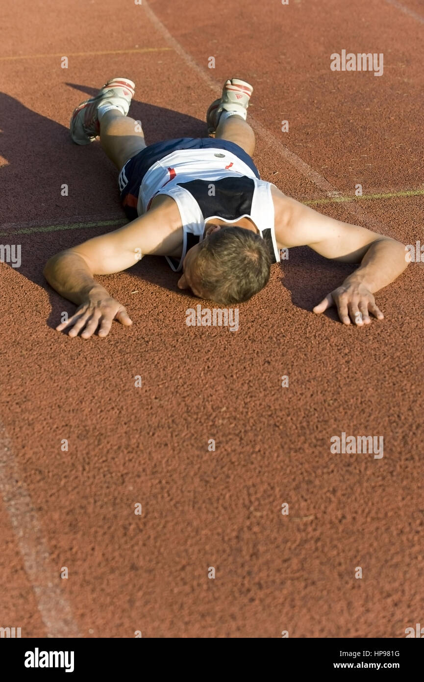 Model released , Sportler liegt erschoepft auf der Laufbahn - exhausted sportsman lying on ground - Stock Image