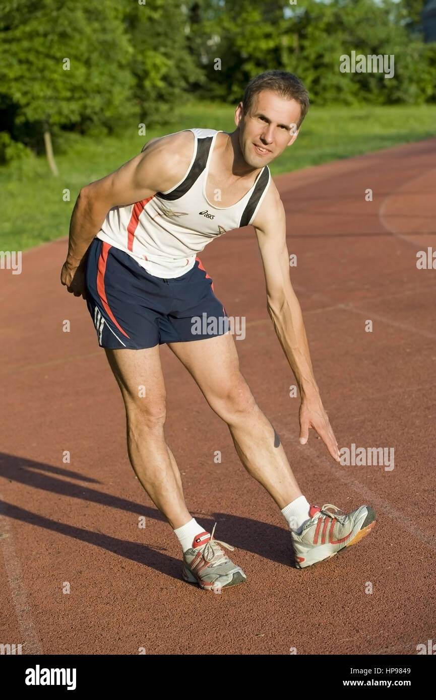 Model released , Sportler beim Stretching - man does stretching - Stock Image