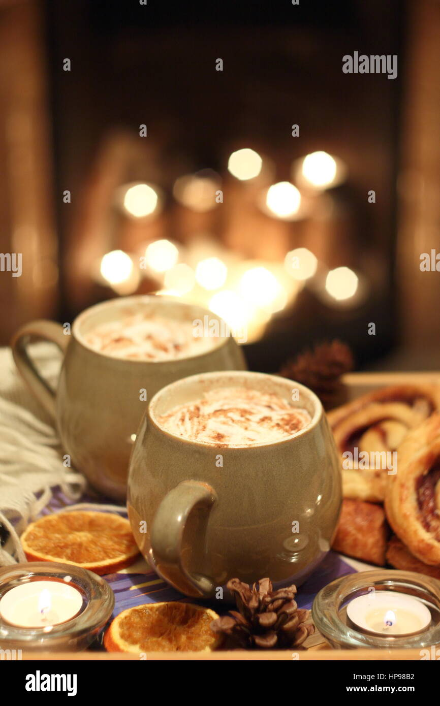 Creamy mugs of mocha - coffee and chocolate - are served with cinnamon buns by a candle lit open fireplace in a - Stock Image