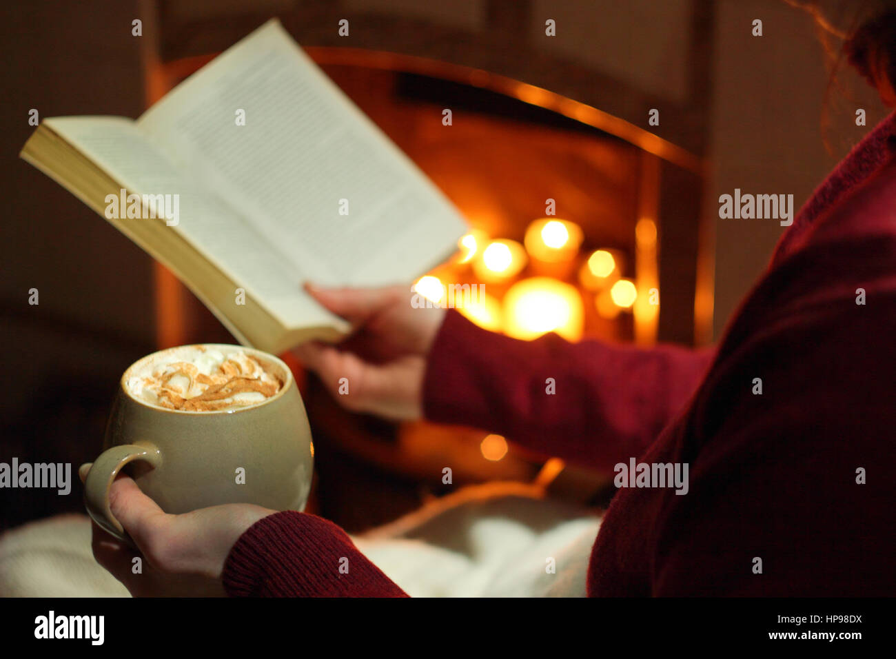 A woman reads a book with a mug of cream topped mocha (coffee and chocolate) by an open fireplace lit with candles - Stock Image