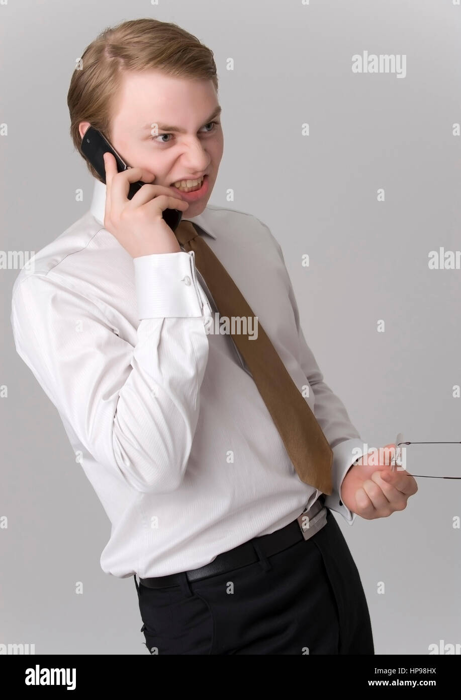 Model released , Zorniger, junger Gesch?ftsmann mit Handy - young businessman with mobile phone Stock Photo