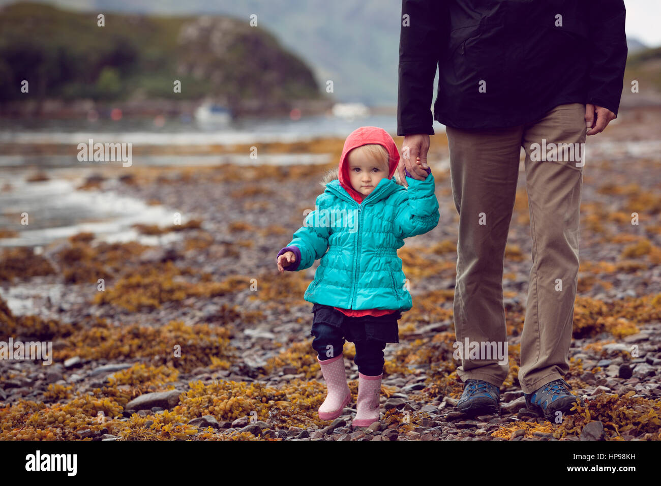 Child and father walking along shore of a Scottish loch - Stock Image