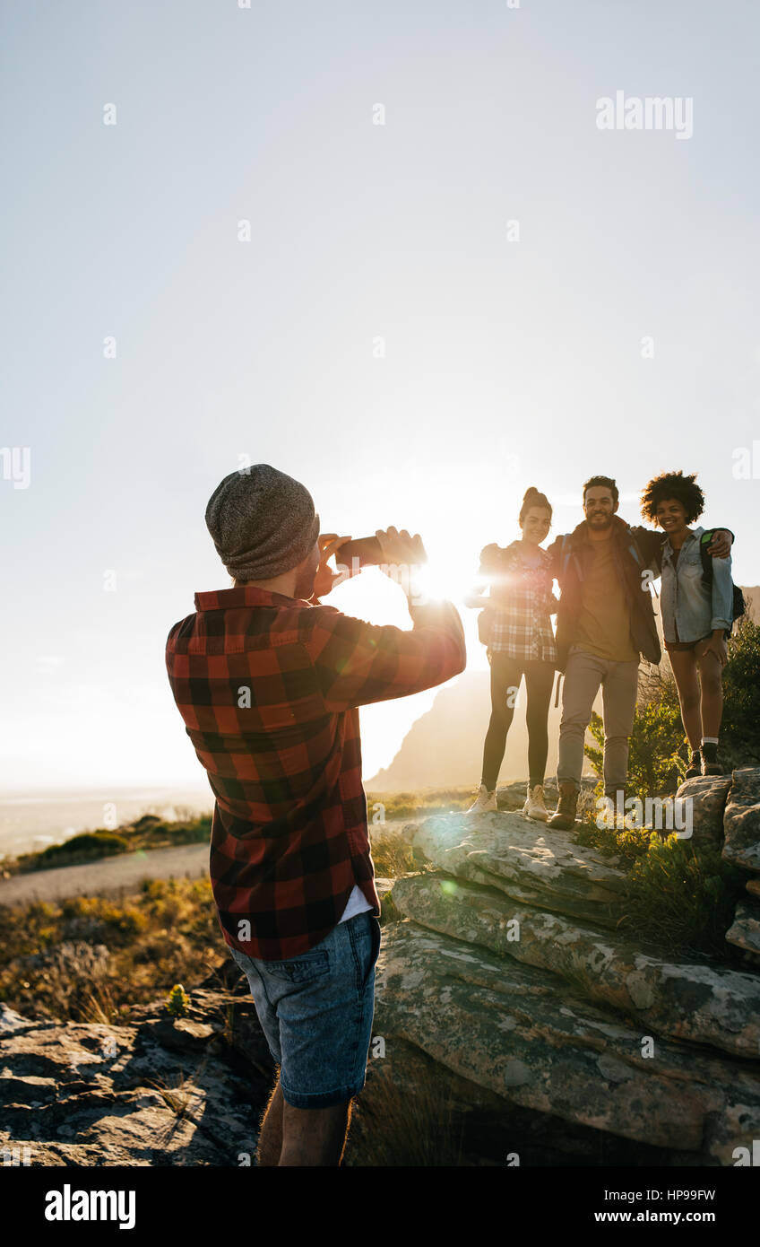 Outdoor shot of young man photographing his  friends in countryside while hiking. Hiker group enjoying during summer - Stock Image