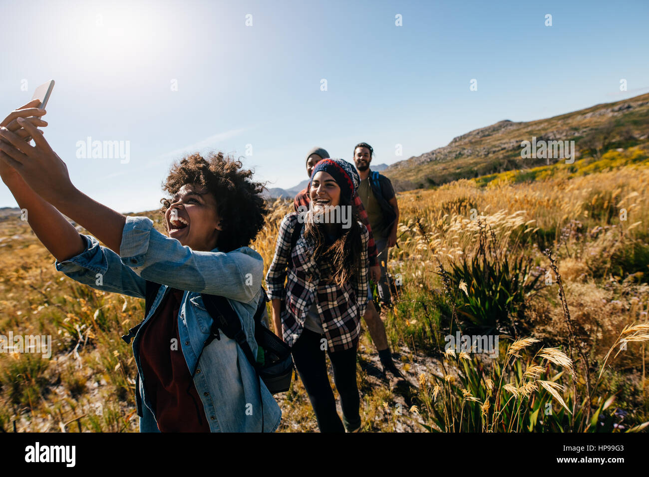 Happy young woman taking pictures of friends while hiking. Group of friends on country walk taking selfie. - Stock Image