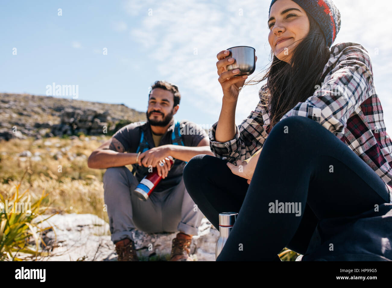 Young woman drinking coffee and resting with friend during hike. Two young friends taking a break during hike. Stock Photo