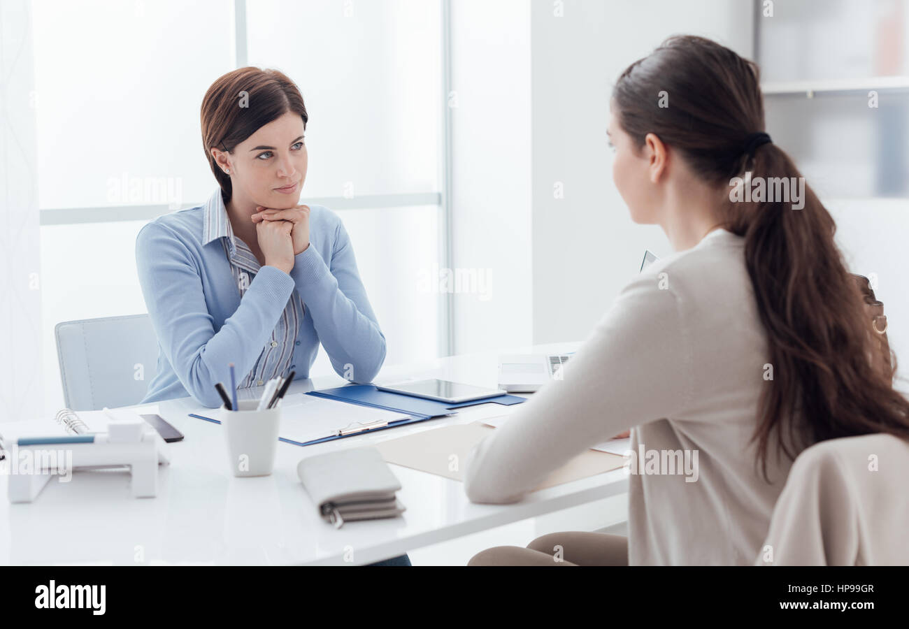 Business meeting in the office and job interview: a female executive is meeting the candidate and talking - Stock Image