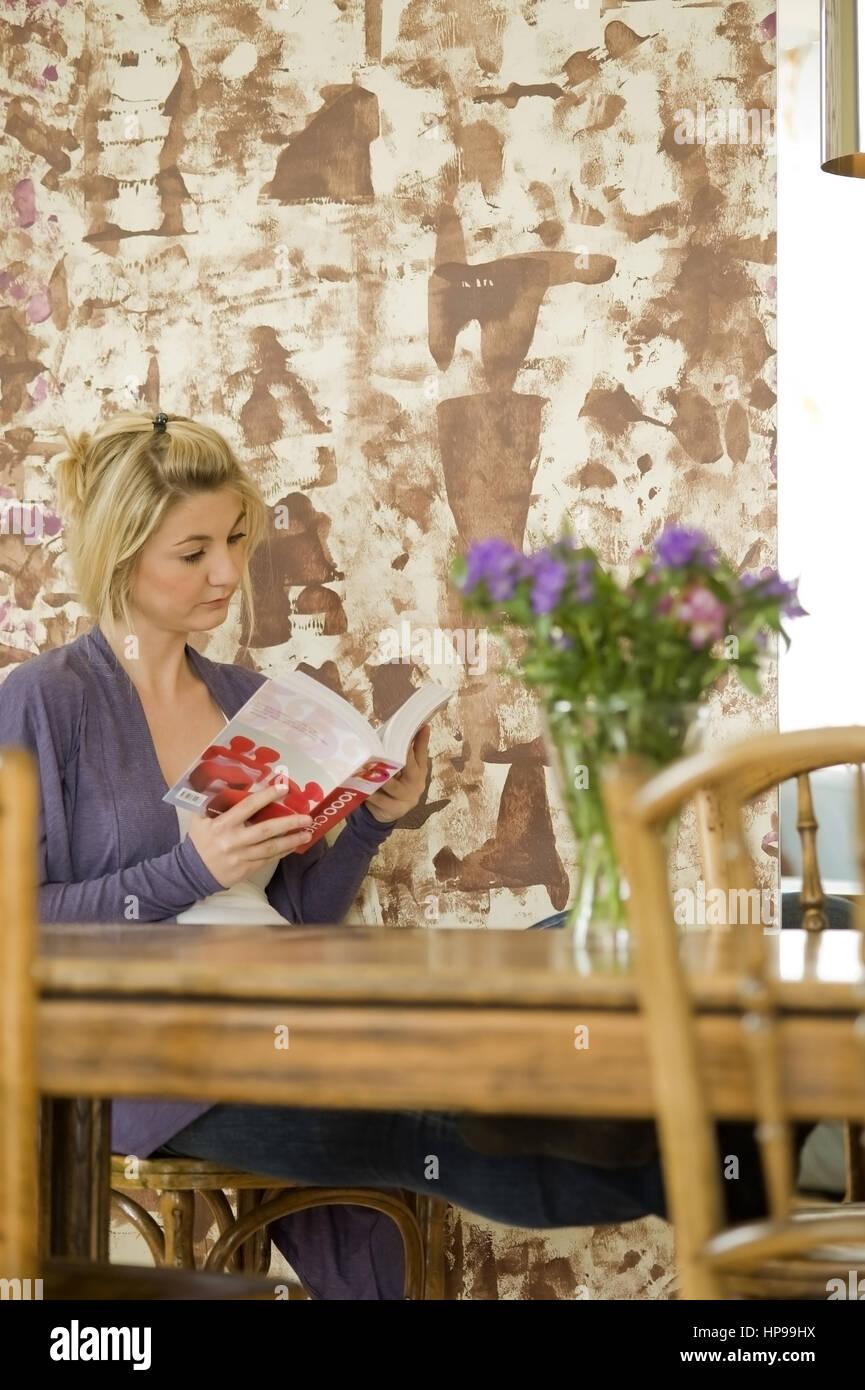 Model released , Junge Frau, 24, sitzt am Tisch und liest ein Buch - woman reading a book - Stock Image