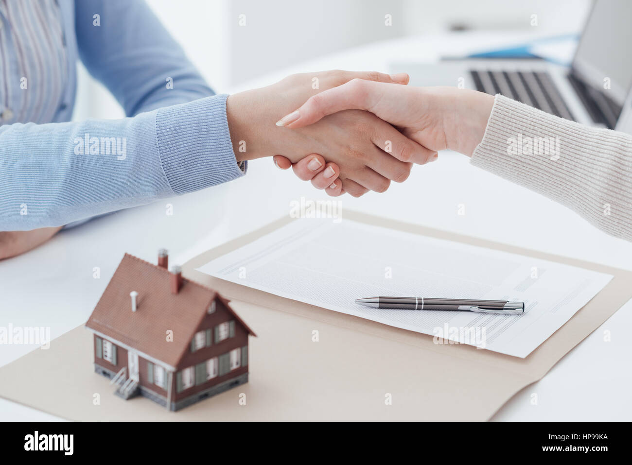Real estate broker and customer shaking hands after signing a contract: real estate, home loan and insurance concept - Stock Image