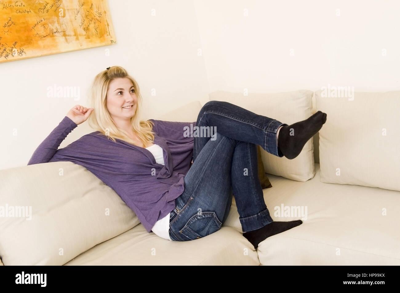 Model released , Junge blonde Frau, 24, sitzt auf einer Couch - woman sitting on couch - Stock Image