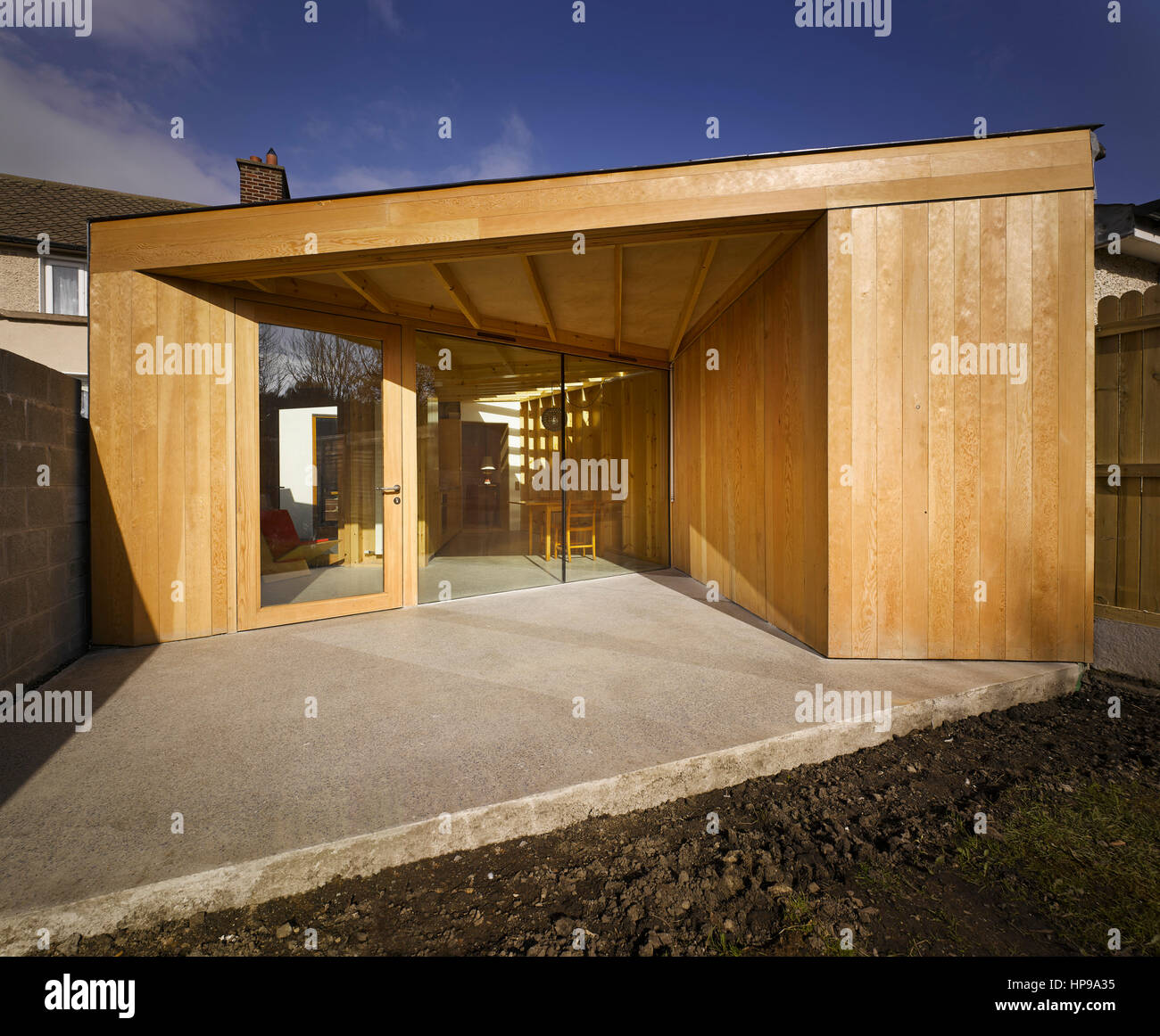 Exterior view of extension showing light in courtyard and through skylight. Rutland Avenue, Crumlin, Ireland. Architect: - Stock Image