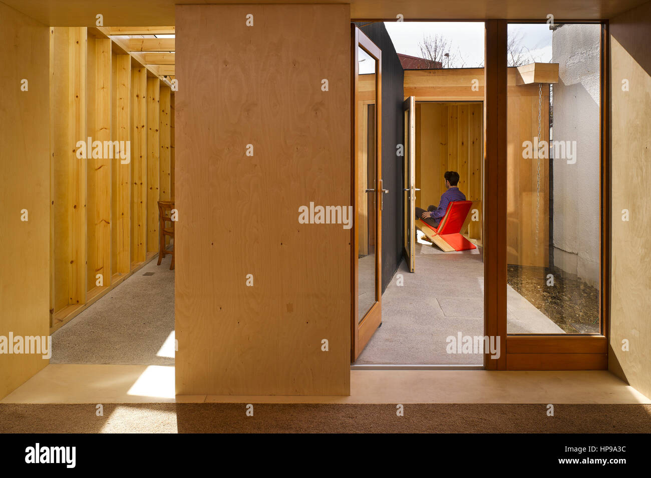 Interior view from sitting room showing kitchen area and courtyard with figure seated. Rutland Avenue, Crumlin, - Stock Image
