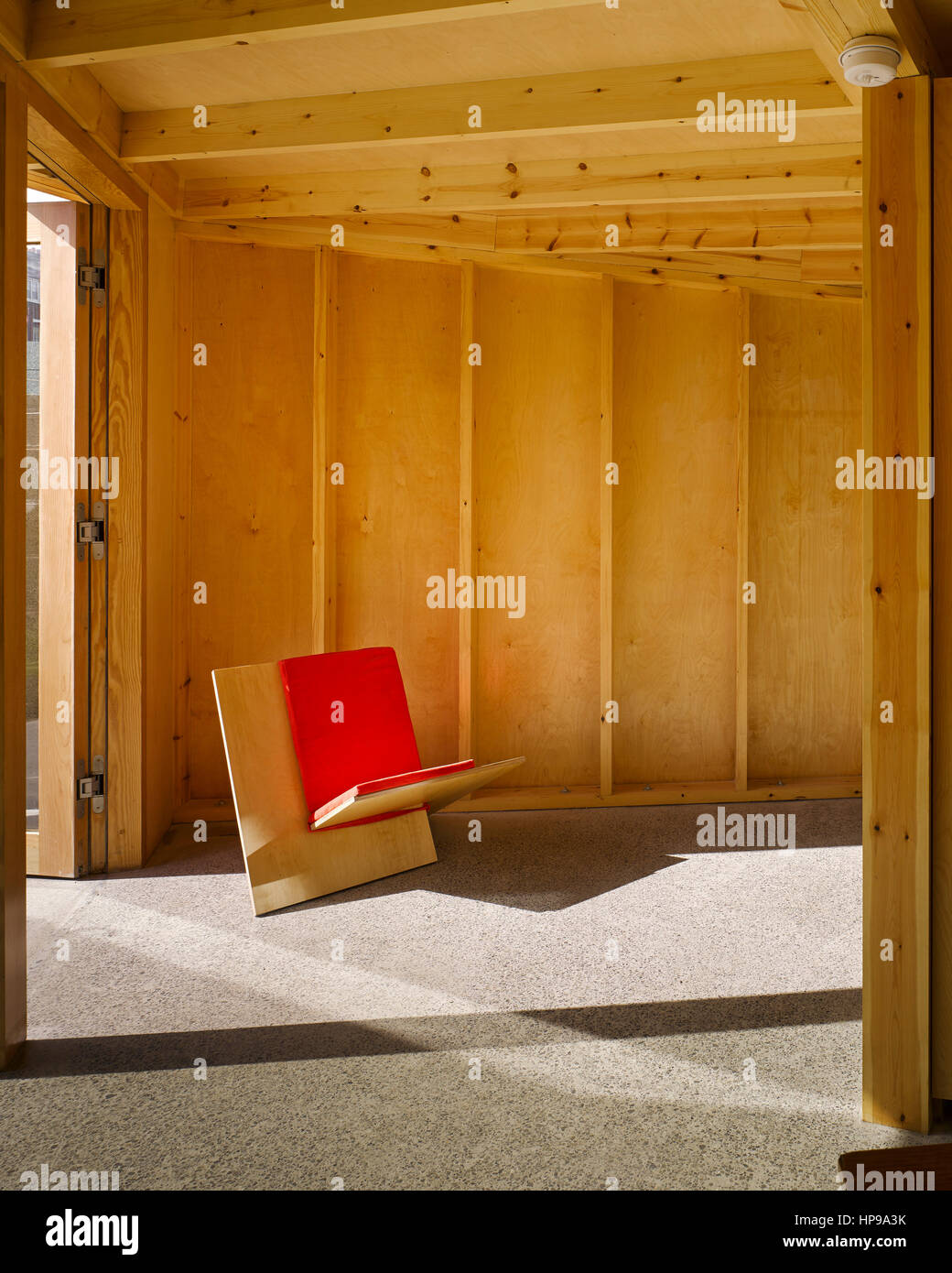 Interior view of new sitting area showing 2 element ply chair with cushion. Rutland Avenue, Crumlin, Ireland. Architect: - Stock Image