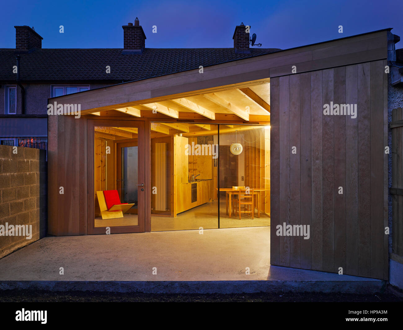 Exterior view at dusk showing interior lit by one light source. Rutland Avenue, Crumlin, Ireland. Architect: Eamon - Stock Image