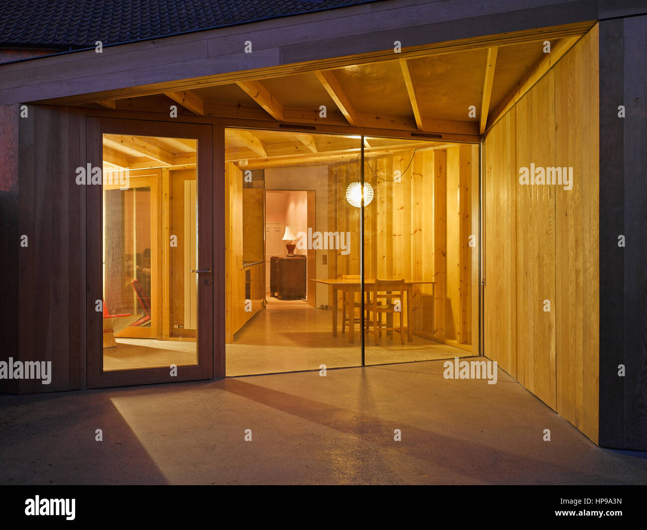 Exterior view at dusk showing interior of extension leading to sitting room. Rutland Avenue, Crumlin, Ireland. Architect: - Stock Image