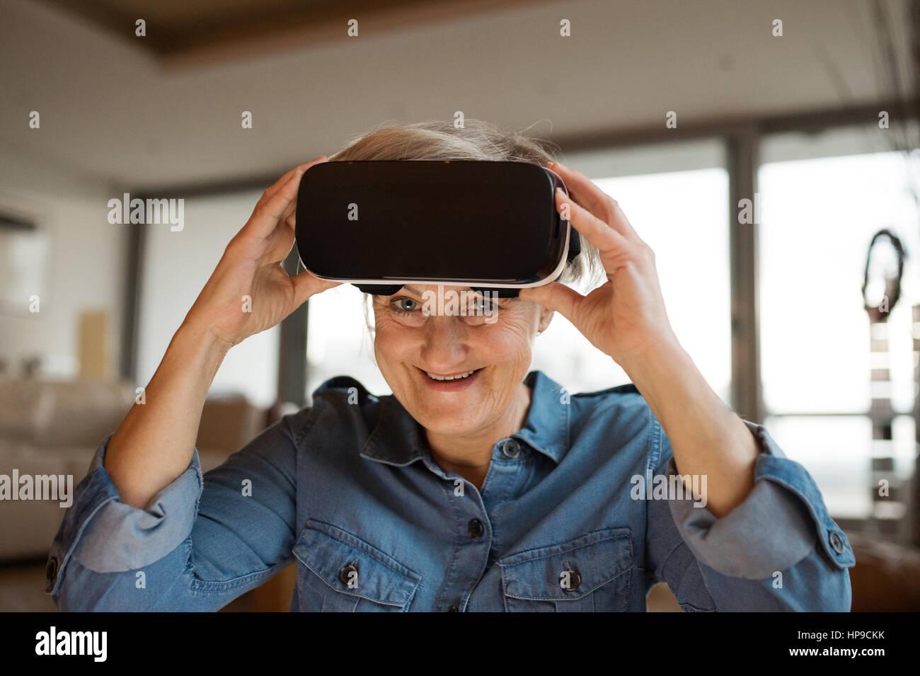 Senior woman wearing virtual reality goggles at home - Stock Image