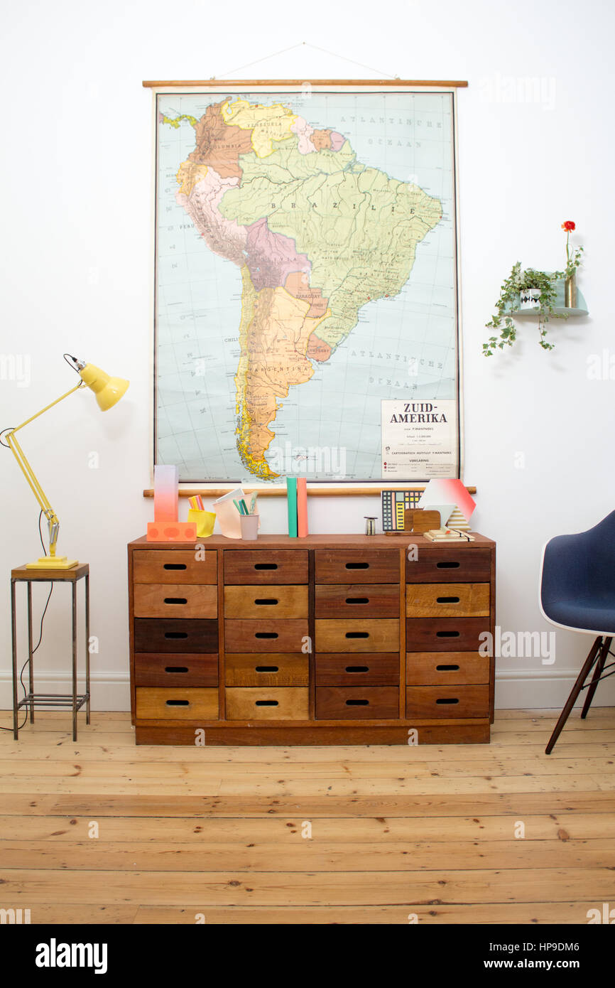 A Mid-Century modern chest of drawers in a home office with an antique map hanging above - Stock Image