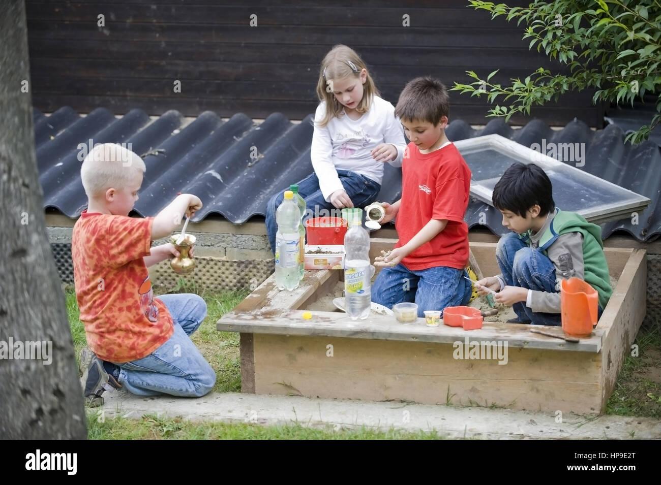 Kinder spielen im Sandkasten - children playing in sandpit - Stock Image