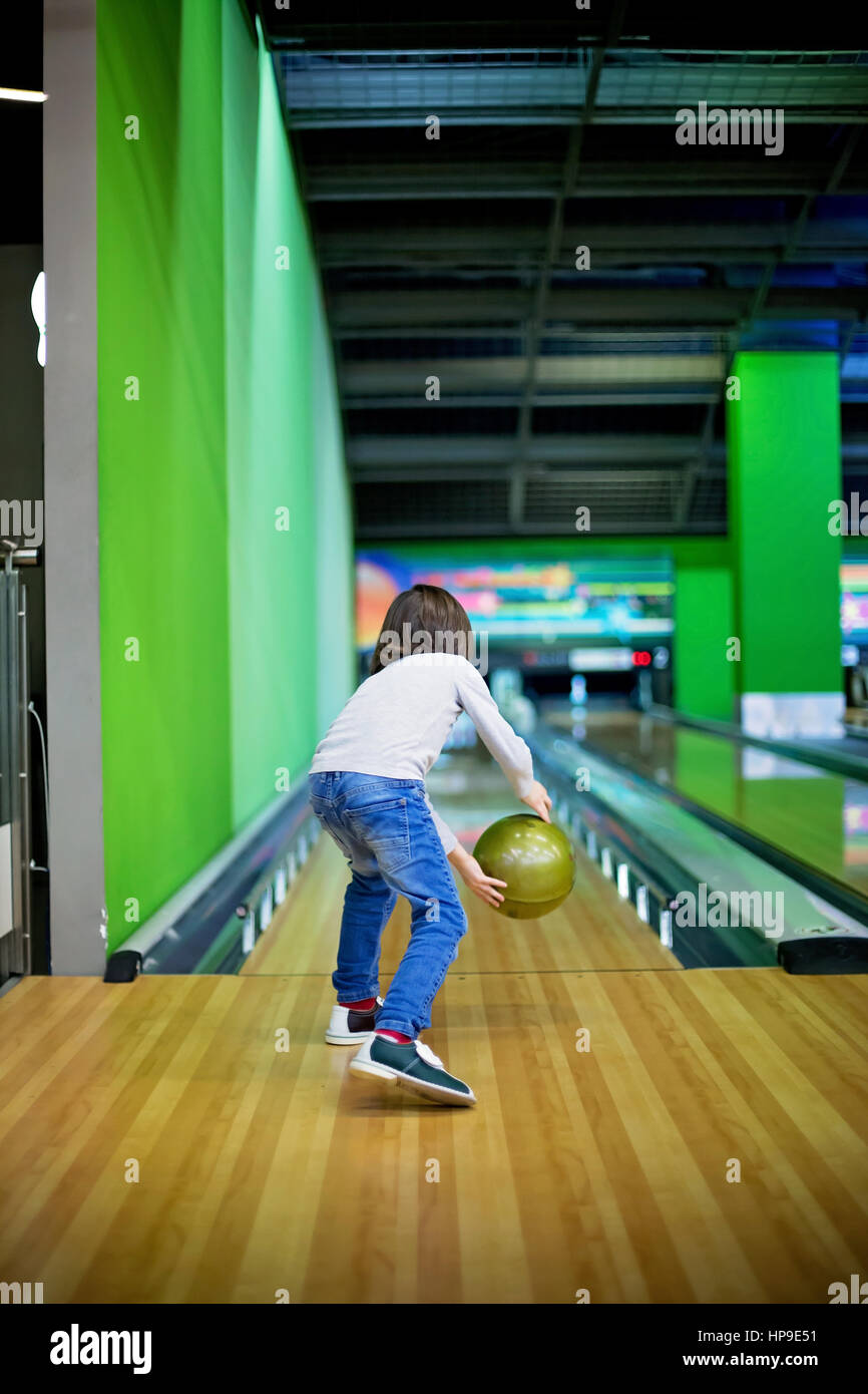 Young boy, playing bowling for the first time, indoors - Stock Image