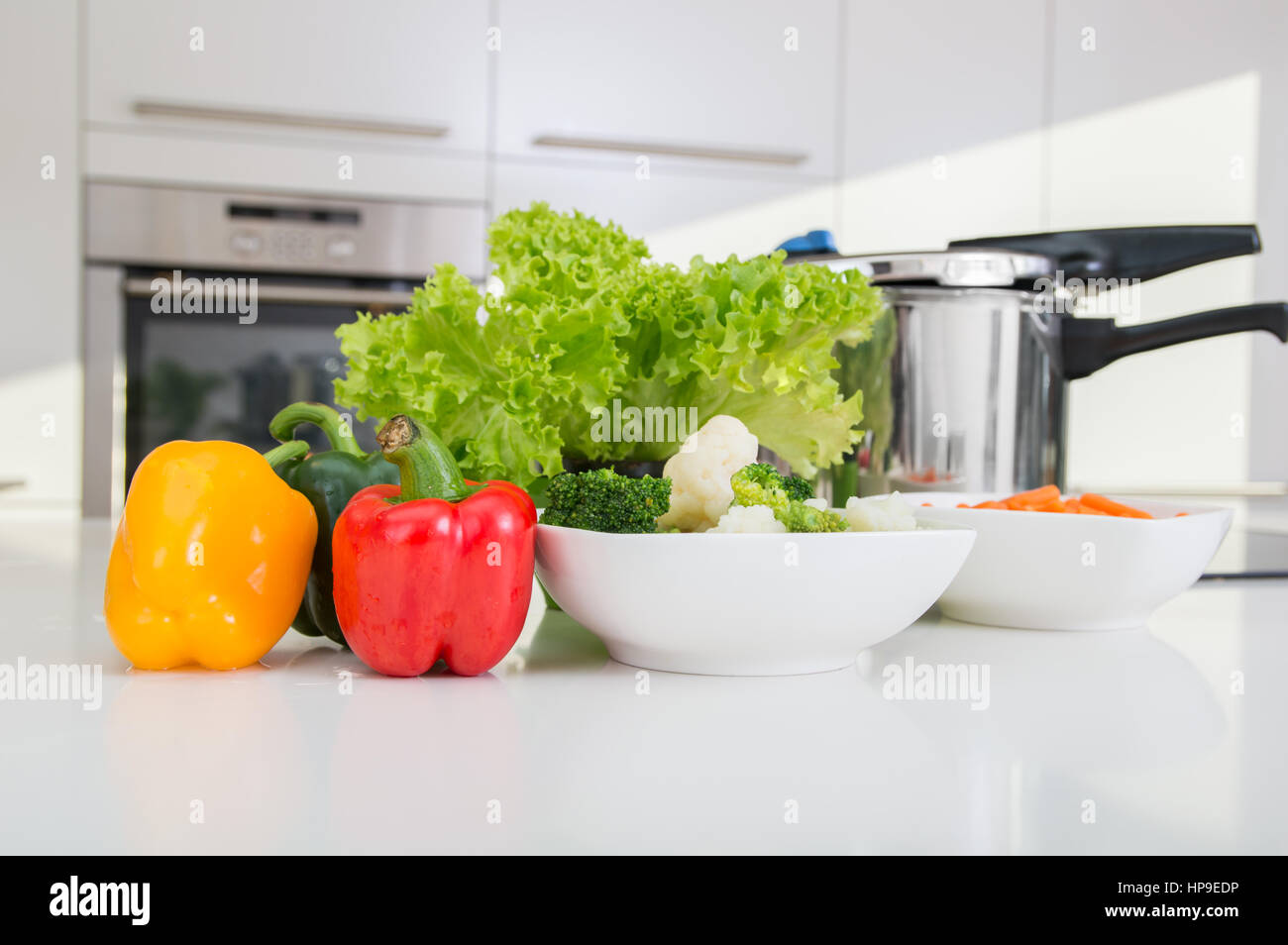 Pressure cooker and vegetables prepared to be cooked. - Stock Image