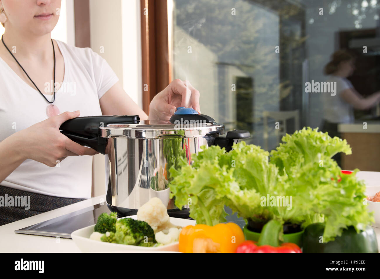 Woman uses pressure cooker to cook a meal. Conception of healthy nutrition. - Stock Image
