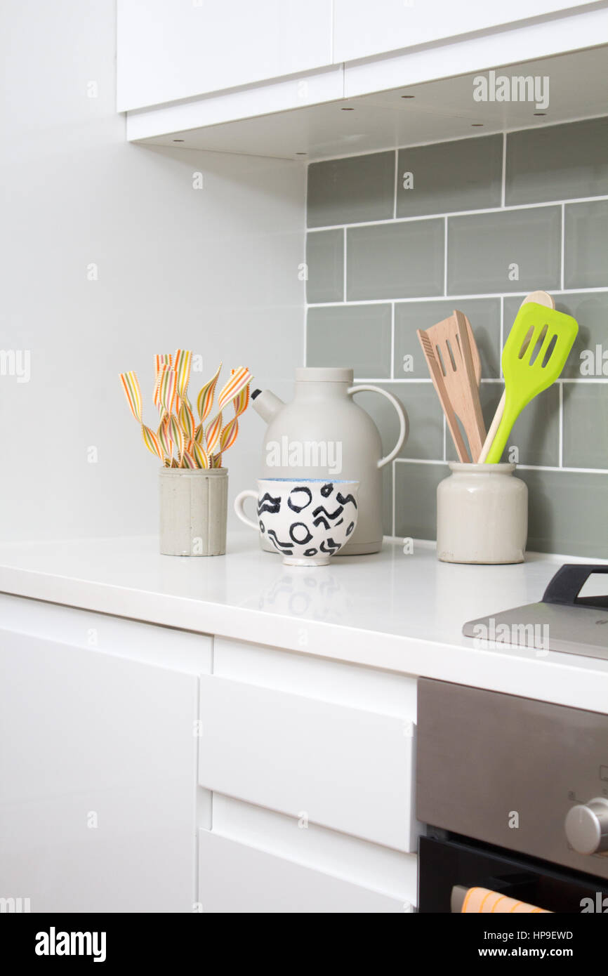 Kitchen utensils sit in pots beside the hob in a modern kitchen - Stock Image